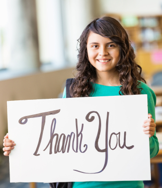 """A young Hispanic girl holds up a sign saying """"Thank You"""""""