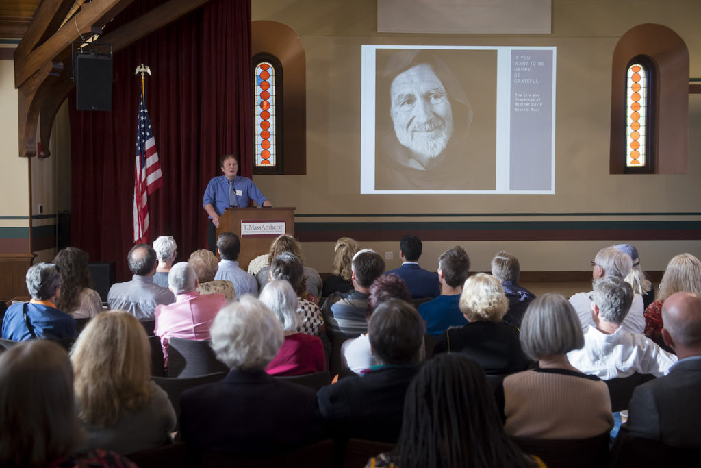 Director of SCUA, Rob Cox, giving a presentation with a photo of monk Br. David on the screen