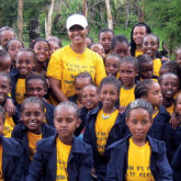 Lily Yoseph surrounded by student girls in yellow and blue shirts.