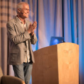 Paul Hawken - tall man with white hair speaking at a podium