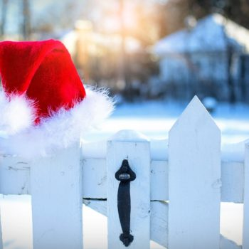 santa's hat hanging on a white fence post
