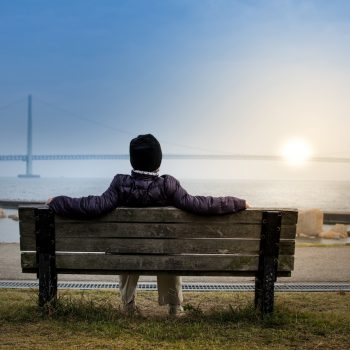 Person sitting on a bench overlooking a bay.