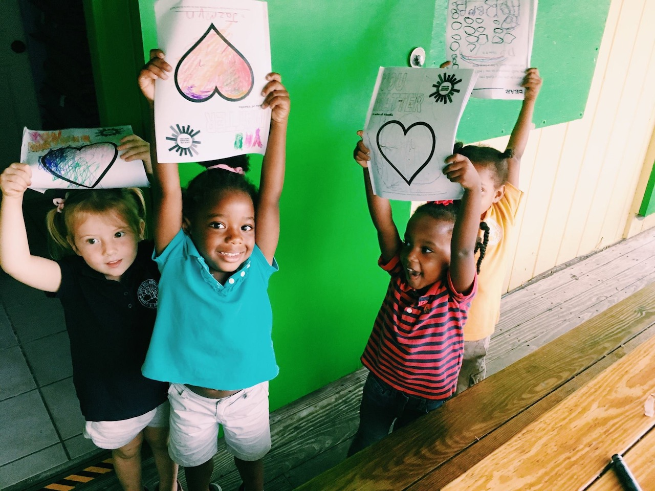Kids holding up hearts drawn and colored on paper
